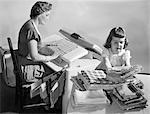 1950sHOUSEWIFE PRESSING LINENS AS DAUGHTER FOLDS & STACKS THEM ON TABLE
