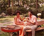 1970s SMILING AFRICAN AMERICAN COUPLE MAN WOMAN DRINKING BEER AT BACKYARD BARBECUE
