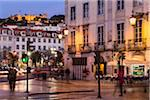 View of the hilltop fortification Castelo de Sao Jorge from an illuminated street corner at Praca Dom Petro IV (Rossio), blue hour, dusk, Donwtown, Lisbon, Portugal