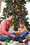 A mother and two children by a large Christmas tree unwrapping presents.