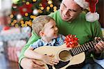 A father and son sitting by a Christmas tree, playing a guitar.