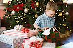 A child sitting by a Christmas tree unwrapping a parcel.