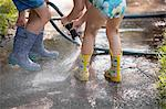 Children playing with water hose on sidewalk