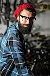 Hipster bike mechanic standing