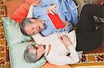 Couple using digital tablet on floor