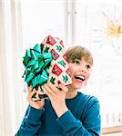 Boy (10-11) shaking Christmas present