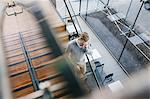 Finland, Young businessman walking downstairs and talking on phone
