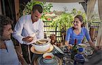Waiter serving young couple soup, Marrakesh, Morocco