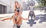 Teenage girls riding skateboard and BMX bicycle on sunny urban street