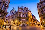 South building at Piazza Vigliena (Quattro Canti) with scooter taxis on Corso Vittorio Emanuele at dusk in Palermo in Sicily, Italy