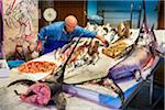 Fishmonger placing fish on ice in display at Vucciria Market in Palermo, Sicily, Italy
