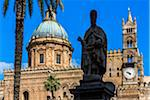 Silhouetted statue of Archbishop in front of the dome and clock tower of the Palermo Cathedral in historic Palermo in Sicily, Italy
