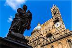 Silhouetted statue of a saint in front of clock tower and dome at the Palermo Cathedral in historic Palermo in Sicily, Italy