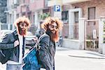 Young male hipster twins with red hair and beards strolling on road
