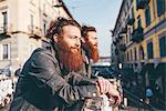 Young male hipster twins with red hair and beards looking out from city footbridge