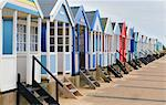 Angled view of a row of multi-coloured beach huts, Southwold, Suffolk, UK
