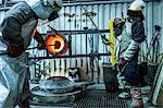 Male foundry worker working with bronze melting pot in bronze foundry