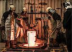 Male foundry workers winching white hot melting pot in bronze foundry