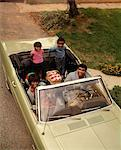 1970s AFRICAN AMERICAN FAMILY OF FOUR SEATED IN CONVERTIBLE CAR FATHER MOTHER SON DAUGHTER LOOKING AT CAMERA