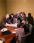 1950s 1960s SEVEN BUSINESS PEOPLE GATHERED AROUND IN A MEETING EXAMINING A PROJECT