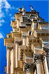 Low angle view of the ornate mouldings and pillars of the Cathedral of Saint George (Duomo di San Giorgio) against a blue sky in Ragusa in Sicily, Italy