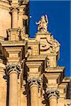Decorative mouldings and statue on the Cathedral of Saint George (Duomo di San Giorgio) against a blue sky in Ragusa in Sicily, Italy