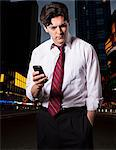 Stressed businessman in city with smartphone