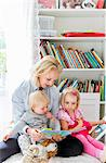 Mother reading book to her daughters