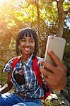 Young woman in forest, using smartphone, having video call, Cape Town, South Africa