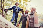 Grandparents walking grandson on log in autumn park