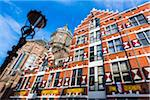 Historical facade of the Verf en Vernis Factory with the tower of the Church of Saint Nicholas in Amsterdam, Holland