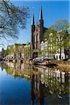 Tranquil view of the De Krijtberg Church along the Singel Canal in Grachtengordel in Amsterdam, Holland