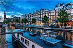 Table and chairs on top of a houseboat moored along the Prinsengracht canal at dusk in Amsterdam, Holland
