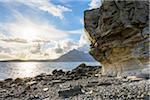 Rock face of sea cliff with honeycomb weathering and sun shining over Loch Scavaig on the Isle of Skye in Scotland, United Kingdom