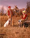 1960s TWO MEN HUNTERS SITTING STANDING WITH HUNTING DOGS HOLDING BRACE OF HARVESTED PHEASANT
