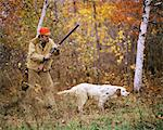1960s 1970s MAN HUNTER WITH SHOTGUN IN AUTUMN LANDSCAPE PHEASANT HUNTING WITH ENGLISH SETTER GUN DOG ON POINT
