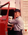 1950s 1960s SMILING MAN DELIVERY DRIVER WEARING CAP AND UNIFORM LOOKING AT CAMERA STEPPING INTO CAB THROUGH OPEN TRUCK DOOR