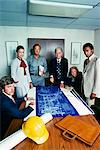 1970s GROUP OF 6 MEN AND WOMEN IN BUSINESS MEETING ROOM LOOKING AT CAMERA OVER BLUEPRINTS