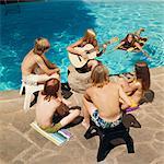 1970s 6 TEENS AROUND SWIMMING POOL LISTENING TO GIRL PLAYING GUITAR