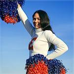 1960s SMILING TEEN GIRL CHEERLEADER IN WHITE SWEATER HOLDING RED AND BLUE POMPOMS ONE ARM RAIDED OTHER AT HIP LOOKING AT CAMERA