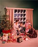 1960s MAN WOMAN MOTHER FATHER TWO TEENAGERS BOY GIRL SON DAUGHTER AROUND CHRISTMAS TREE OPENING PRESENTS