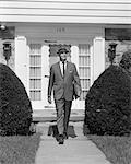 1950s BUSINESSMAN LEAVING SUBURBAN HOUSE HOLDING BRIEFCASE WALKING DOWN SIDEWALK