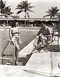1930s COUPLE TROPICAL HOTEL SWIMMING POOL SIDE WOMAN BATHING SUIT MAN SITTING DIRECTORS CHAIR CASUAL CLOTHES MIAMI BEACH FL USA