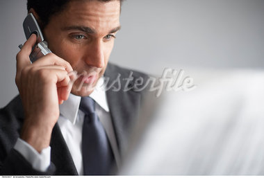 Businessman with Cellular Phone Reading Newspaper    Stock Photo - Premium Rights-Managed, Artist: Jerzyworks, Code: 700-00610017