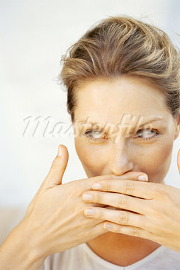 close-up of a young woman covering her mouth with her hands Stock Photo - Premium Royalty-Freenull, Code: 618-00661777