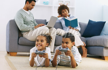 Parents sitting on sofa reading book and working on laptop with children playing computer game (9 11) Stock Photo - Premium Royalty-Freenull, Code: 627-00852876