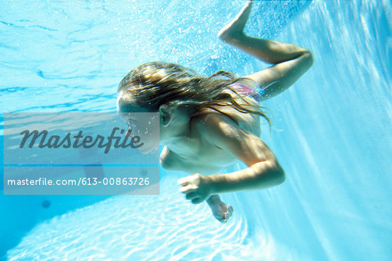 Teenage girl (14-16) swimming underwater in swimming pool Stock Photo - Premium Royalty-Freenull, Code: 613-00863726