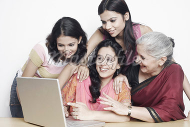 Four women in front of a laptop Stock Photo - Premium Royalty-Freenull, Code: 630-01077862