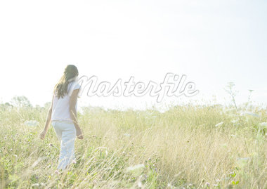 Girl walking through tall grass in field Stock Photo - Premium Royalty-Freenull, Code: 633-01274193