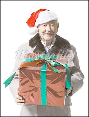 Older man in Santa hat holding a Christmas present Stock Photo - Premium Royalty-Freenull, Code: 640-01364991